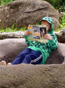 Kickin' back with the map- trying to memorize the route to the dinosaur maze, which is his favorite activity at the zoo